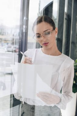 businesswoman writing on paperwork
