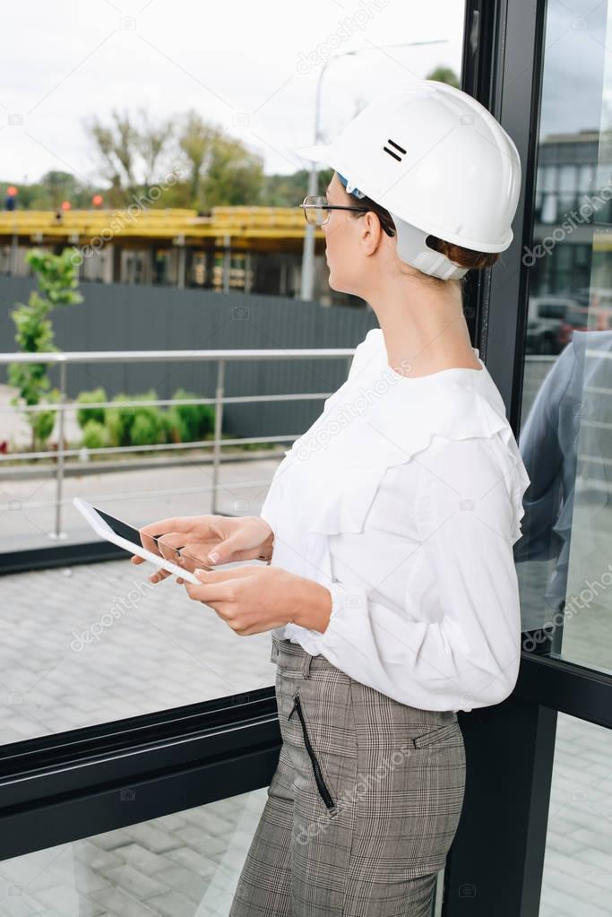 businesswoman in hardhat with digital tablet