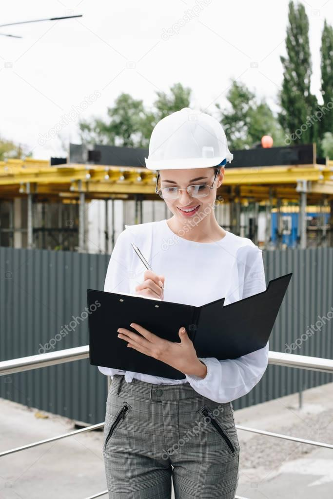 businesswoman at construction site holding folder