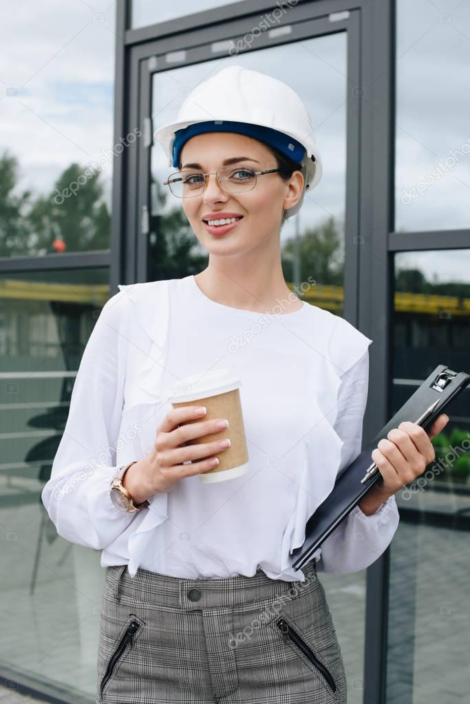 engineer in hardhat holding clipboard and coffee