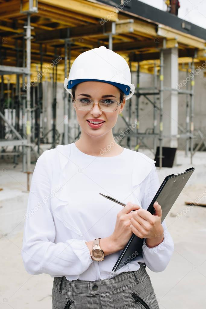 engineer in hardhat holding clipboard