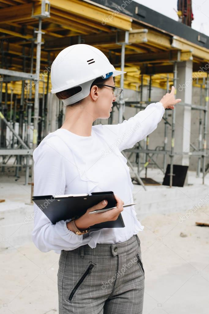 engineer pointing at construction site
