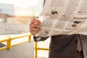 man with newspaper in bus