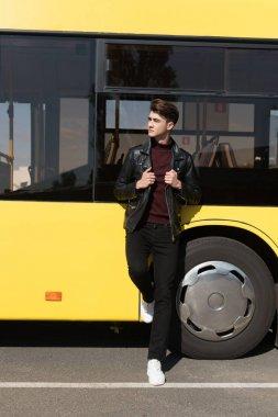 man standing near city bus