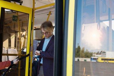 man checking time in bus