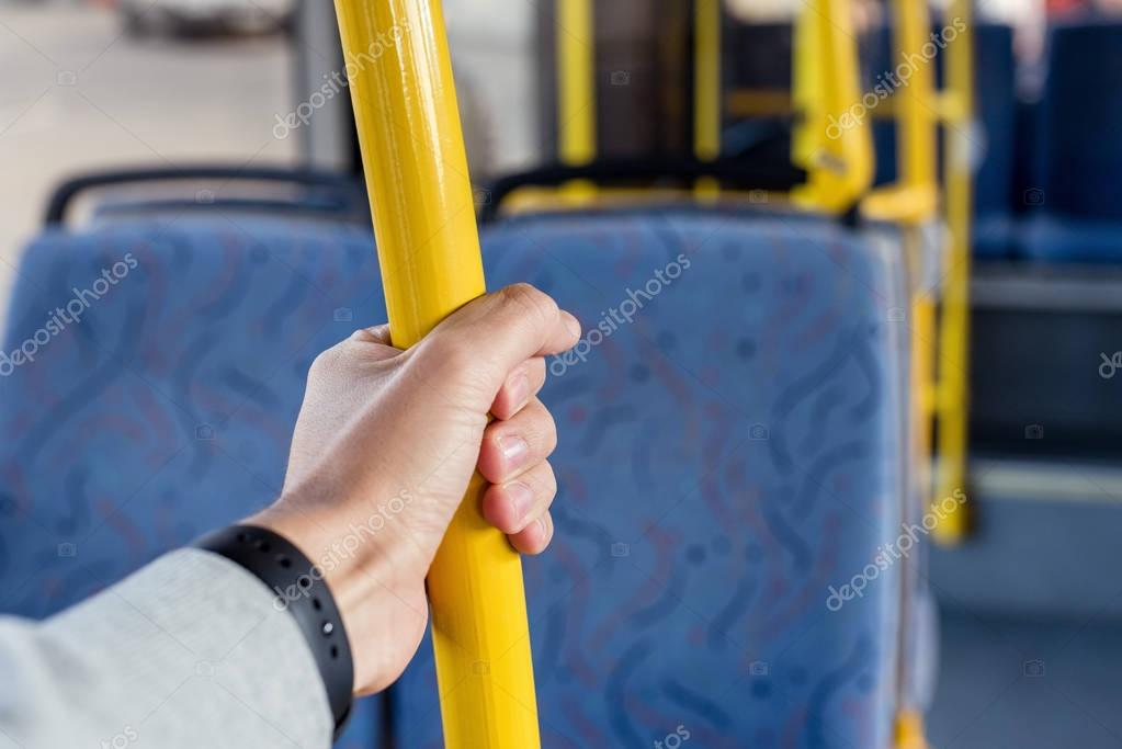 man holding bus handle