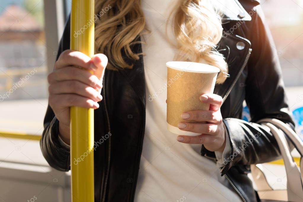 woman with coffee to go in bus