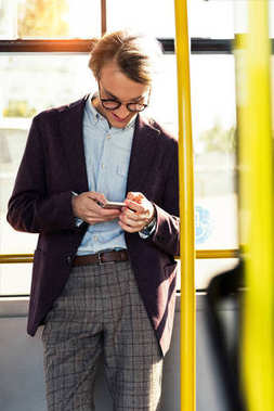 smiling man with smartphone in bus