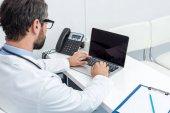 Fotografie doctor using laptop