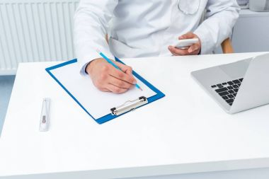 doctor using smartphone and writing in clipboard