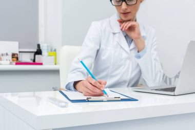 female doctor writing in clipboard