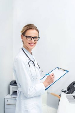 female doctor writing in clipboard