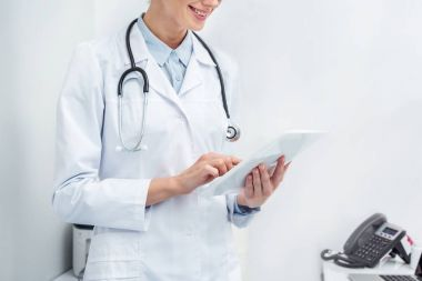 Cropped shot of female doctor using digital tablet stock vector