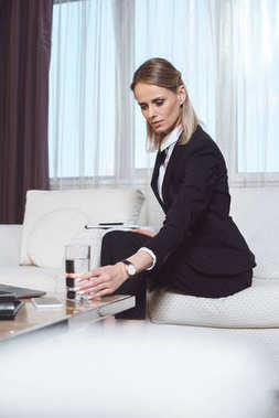 tired businesswoman with glass of water