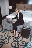 donna di affari che utilizza computer portatile nella camera dalbergo