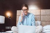 Fotografie businesswoman using laptop in hotel room