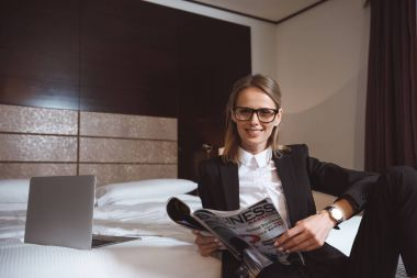 businesswoman reading magazine in hotel