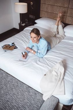 businesswoman writing in notebook on bed