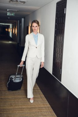 businesswoman with suitcase in hotel
