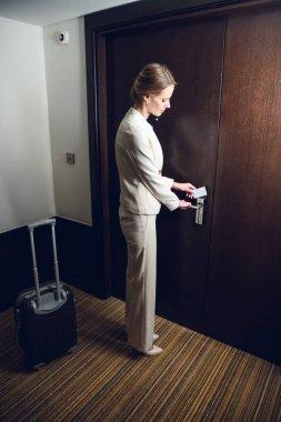 businesswoman opening hotel room door