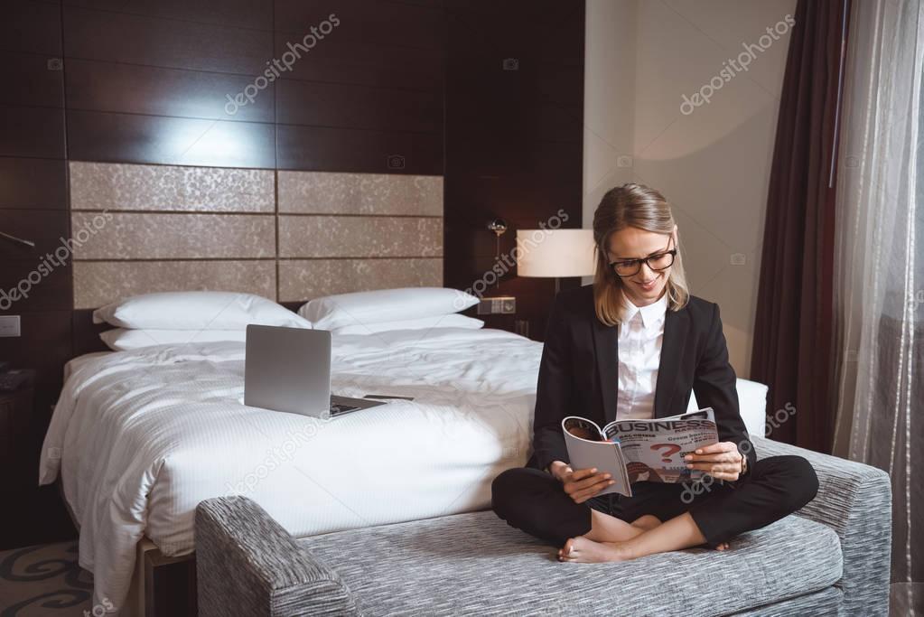 businesswoman reading magazine in hotel