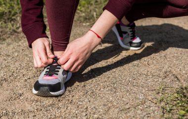 woman lacing shoe