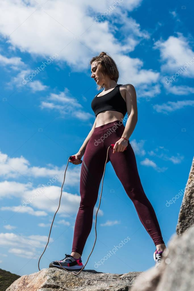 woman on rock with jumping rope