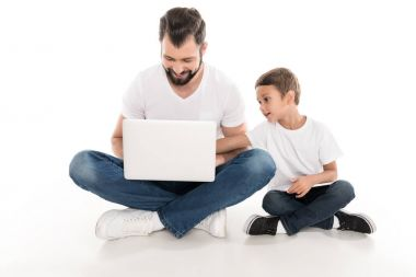 Smiling father and little son using laptop together isolated on white stock vector