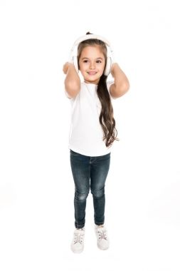 Smiling little girl listening music in headphones isolated on white stock vector