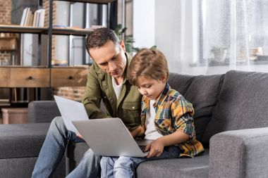 father and son using laptops