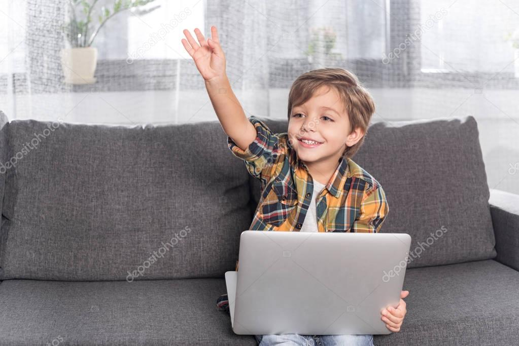 boy with laptop sitting on couch