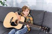 Fotografie malý chlapec s akustická kytara