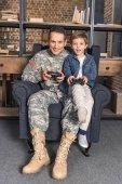 Fotografie Vater und Sohn spielen Konsole mit gamepads