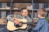 Fotografie Mann des Militärs Gitarre für Sohn