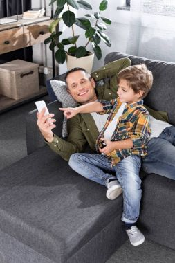 father and son with smartphone
