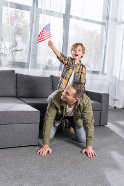 Smiling father and little son with american flag piggybacking together at home stock vector