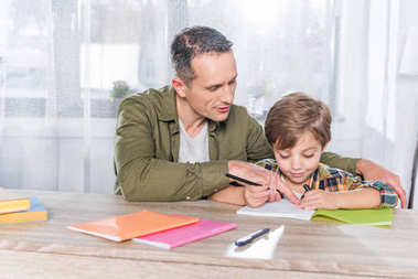 Father and adorable son doing homework together at home stock vector