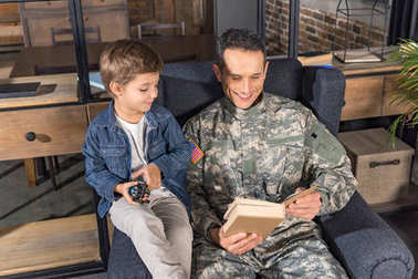 military father and son reading book
