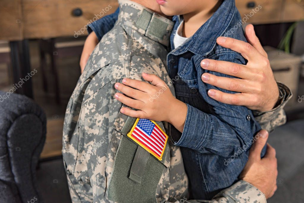 embracing military father and son