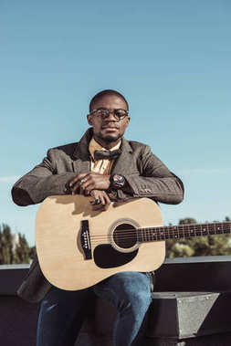 Young african american man in stylish clothes and glasses, posing with guitar stock vector