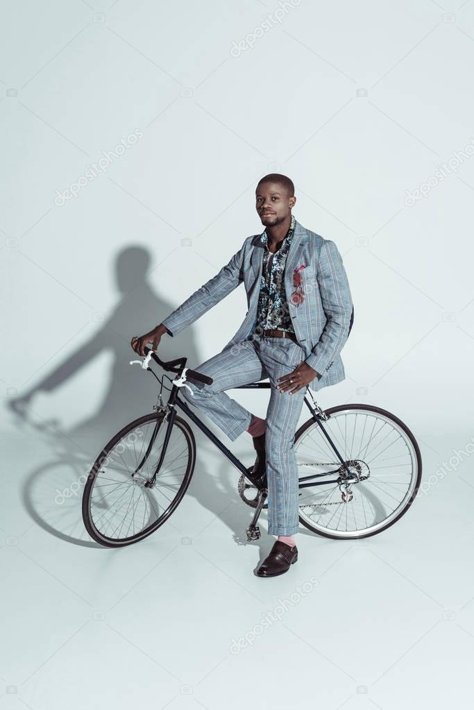 Fashionable man posing on bicycle