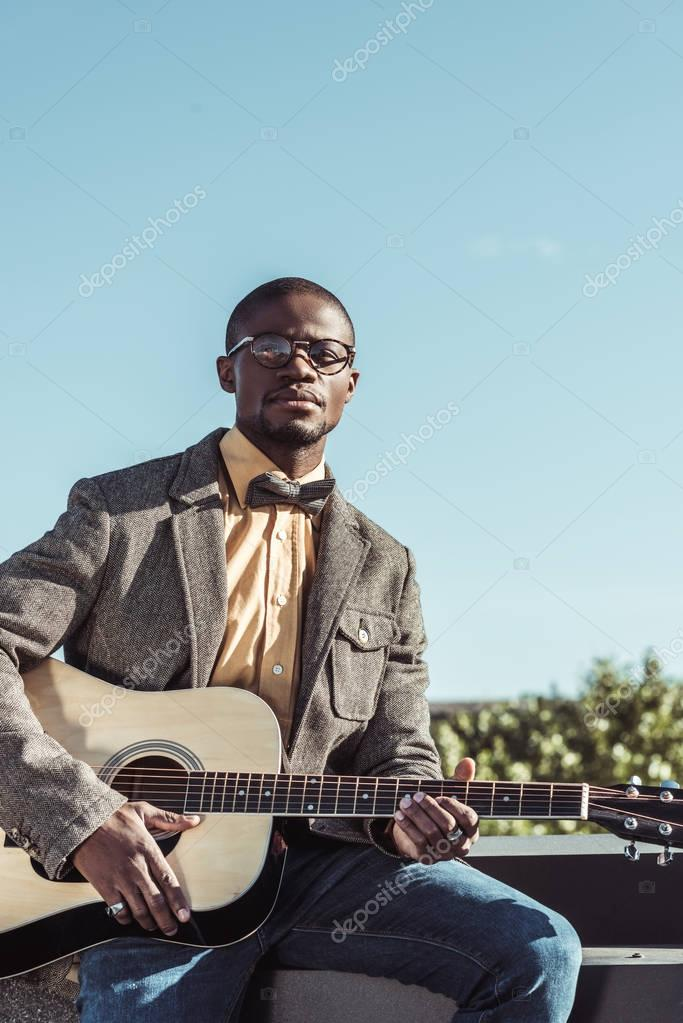 Stylish african american man playing guitar