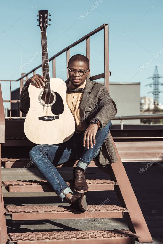 Young man posing on stairs with guitar