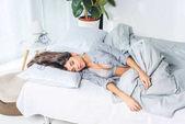 Mladá žena v prádle na posteli