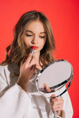 Beautiful teenage girl applying lipstick isolated on red stock vector