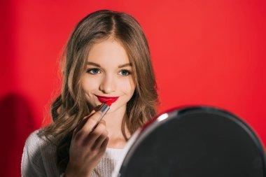 Beautiful teenage girl applying makeup isolated on red stock vector
