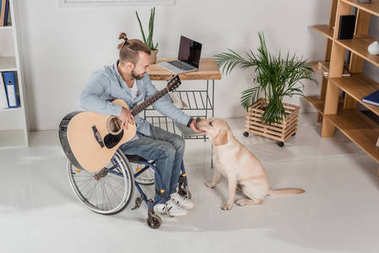 disabled man with guitar petting dog