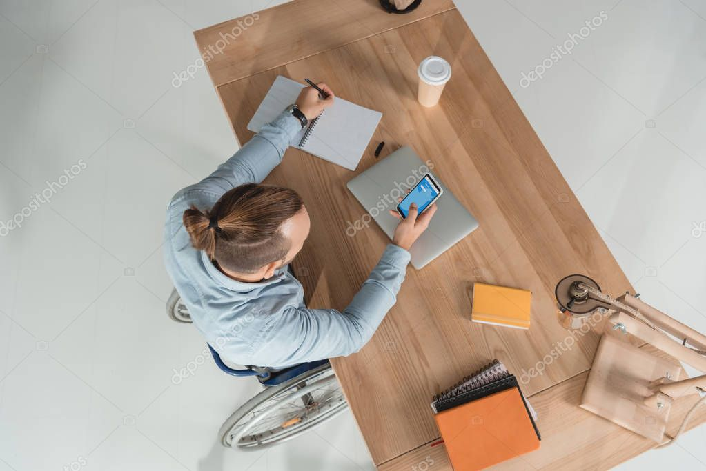man on wheelchair using smartphone