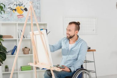 Young happy disabled man on wheelchair painting stock vector