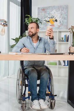 man on wheelchair sitting at worktable